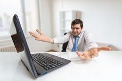 年轻迷茫和缺乏信心的人与膝上型计算机一起使用在办公室 免版税库存图片