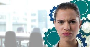 迷茫的妇女在有蓝色嵌齿轮的一个办公室 免版税图库摄影