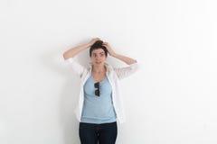 迷茫的少妇扣紧了手在白色背景的一个头 免版税库存图片
