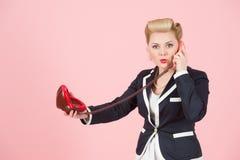迷茫的年轻白肤金发的女孩画象夹克的谈话在嘴唇打电话隔绝在桃红色背景 免版税库存图片