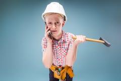 迷茫的建筑工人谈话在有一把锤子的电话在他的手上 免版税库存照片