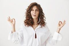 迷茫的逗人喜爱的白种人妇女画象有站立在思考的姿势的时髦理发的用被举的手和禅宗 免版税库存照片