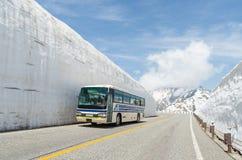 迷离窗口沿雪墙壁的公共汽车移动在日本阿尔卑斯 免版税图库摄影
