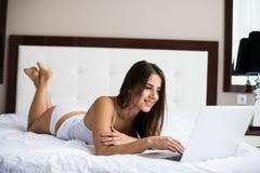 追上在她的社会媒介的妇女,她在与一台便携式计算机的床上放松在一懒惰天 免版税库存图片