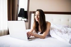 追上在她的社会媒介的微笑的妇女,她在与一台便携式计算机的床上放松在一懒惰天 免版税图库摄影