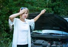 追悼的女孩设法修理一辆残破的汽车 库存照片