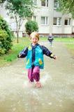 追捕通过水坑的逗人喜爱的女孩雨 免版税库存照片