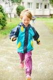 追捕通过水坑的逗人喜爱的女孩雨 免版税图库摄影
