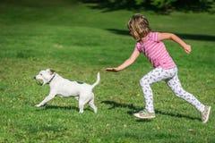 追逐一条狗的女孩在公园 免版税库存图片