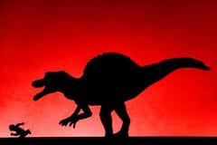 追逐在墙壁上的spinosaurus的阴影人 免版税库存照片