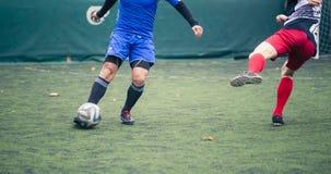 追逐在草领域的两个足球运动员球在足球赛期间 免版税库存照片