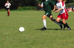 追逐女孩足球的球 免版税库存图片