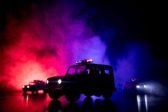 追逐汽车的警车在晚上有雾背景 加速对罪行场面的911应急警车  有选择性的foc 免版税库存图片