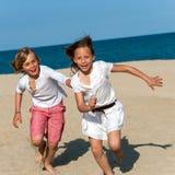 追逐海滩的男孩女孩。 免版税库存图片