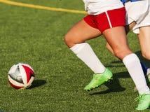 追逐球的两位女性高中足球运动员 库存图片
