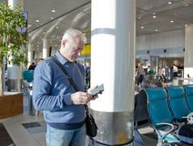 退休年龄的一个人在机场 免版税图库摄影