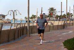 退休年龄的一个人沿江边跑 免版税图库摄影