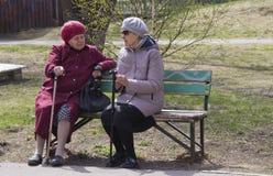 退休年龄的妇女坐长凳并且谈论新闻 免版税库存图片