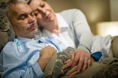 退休的不适的人和有同情心妻子睡觉 免版税库存图片