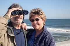 退休的夫妇与双筒望远镜的海滩假期 库存图片