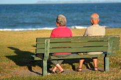 退休的夫妇坐长凳 免版税库存照片