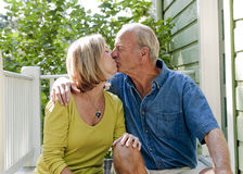 退休的夫妇坐门廊和亲吻 免版税库存照片