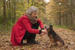 退休的妇女是有同情心的她的狗 库存图片