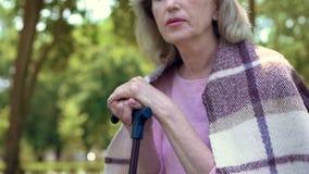 退休的祖母休息室外,倾斜在拐棍,晚年憔悴 库存照片