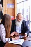 退休的老人学会有美丽的年轻人的新技术片剂 图库摄影
