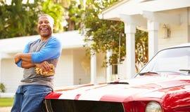 退休的老人清洁被恢复的汽车 库存图片