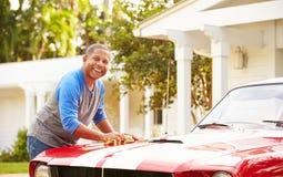 退休的老人清洁被恢复的汽车 免版税图库摄影