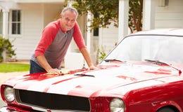 退休的老人清洁被恢复的经典汽车 免版税库存图片