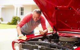 退休的老人清洁被恢复的经典汽车 免版税图库摄影