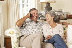 退休的资深夫妇坐沙发在家谈话在电话一起 免版税库存照片