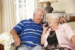 退休的资深夫妇坐沙发在家谈话在电话一起 免版税图库摄影