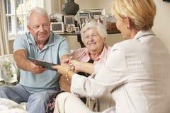 退休的资深夫妇坐沙发谈话与财政顾问 免版税库存照片
