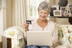 退休的资深妇女在家坐沙发使用膝上型计算机做网上购买 库存图片