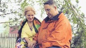 退休年龄一对爱恋和愉快的夫妇非常富感情地坐长凳,妇女神色在她的丈夫 股票视频