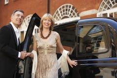 退出伦敦出租汽车的夫妇 免版税图库摄影