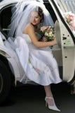 退出大型高级轿车婚礼的新娘汽车 免版税库存图片