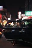 退出汽车的女实业家,当在电话,夜间的时北京 免版税库存图片