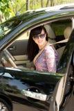 退出汽车的有吸引力的妇女司机 免版税库存图片
