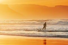 退出水的冲浪者在日落 免版税库存照片