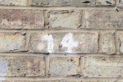 退色的房子号码14白色绘了在墙壁上的标志 图库摄影