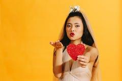 送与红色心脏的美丽的新娘亲吻 库存照片