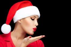 送亲吻的圣诞老人帽子的愉快的圣诞节女孩 免版税库存图片