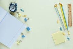 送回学校文具到学校:铅笔,时钟,笔记薄,在黄色背景的统治者 教育,教训 图库摄影