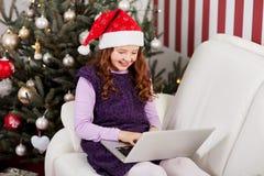 送圣诞节电子邮件的小女孩 免版税图库摄影