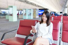 送在手机的妇女sms在机场 库存图片