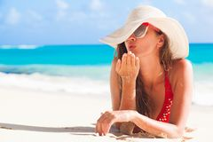 送在热带加勒比海滩的比基尼泳装和草帽的长发女孩一个飞吻 库存图片